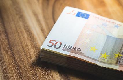 50-Euro-Scheine liegen auf einem Holztisch.
